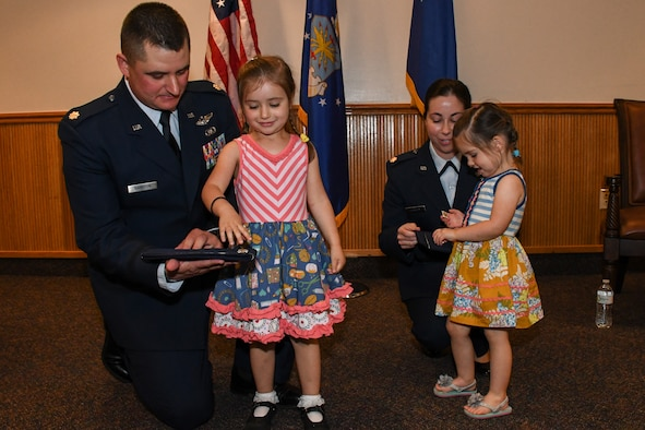 A family affair. Lt. Cols. Shane and Jennifer Garrison receive help from their children during a shared promotion ceremony at Barksdale Air Force Base, La., April 20, 2018.