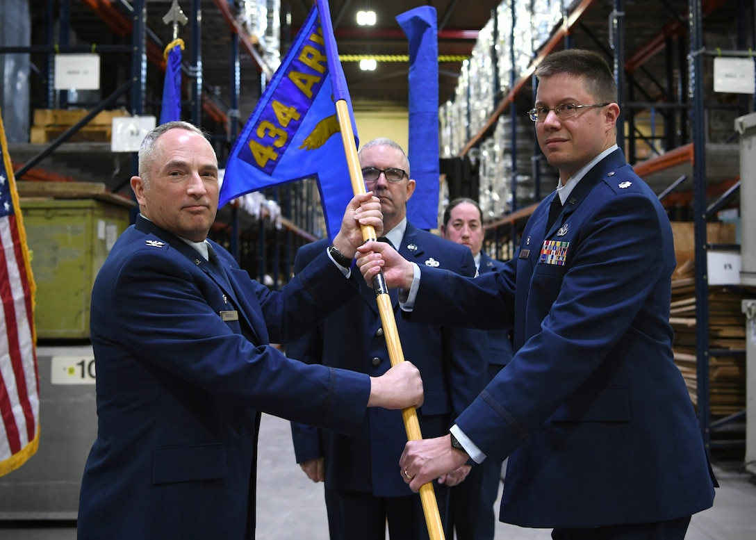 Lt. Col. Christopher Beckley, 49th Aerial Port Squadron, right, accepts the guidon from Col. Scott Russell, 434th Mission Support Group commander, left, as Senior Master Sgt. Kevin Connelly, 49th APS superintendent, center, looks on, during the 49th Aerial Port Squadron re-designation ceremony at Grissom Air Reserve Base, Ind., April 7, 2018. The 49th APS originally constituted on January 29, 1973, as part of the Eastern Air Force Reserve Region assigned to the 514th Military Airlift Wing at McGuire Air Force Base, New Jersey, before being deactivated in 1992 and reassigned to Grissom as the 49th Aerial Port Flight. (U.S. Air Force photo/Staff Sgt. Katrina Heikkinen)