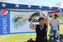 Veteran Roberta May holds her catch above her head during the weigh-in for the biggest fish during the Warrior's Day on the Lake event April 21.