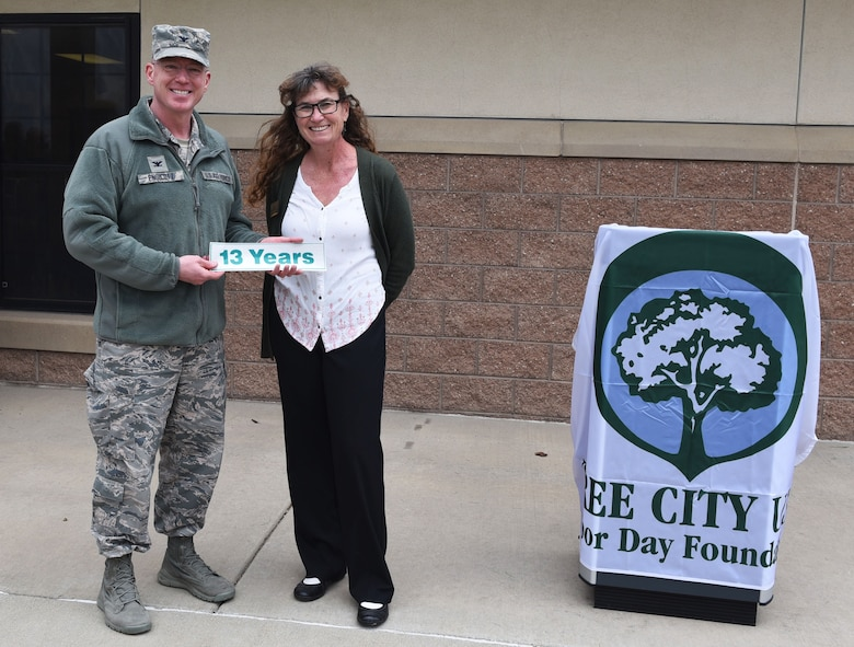 Col. Troy L. Endicott, 460th Space Wing commander, and Ms. Nancy Klasky, a member of the Community Forestry Division for Colorado State, celebrate 13 years Buckley Air Force Base has been a Tree City USA member, April 26, 2018, on Buckley Air Force Base, Colorado. Buckley's involvement in the Tree City USA program underscores the Air Force's commitment to landscape beautification and the environment. (U.S. Air Force Photo by Senior Airman Jessica B. Kind)