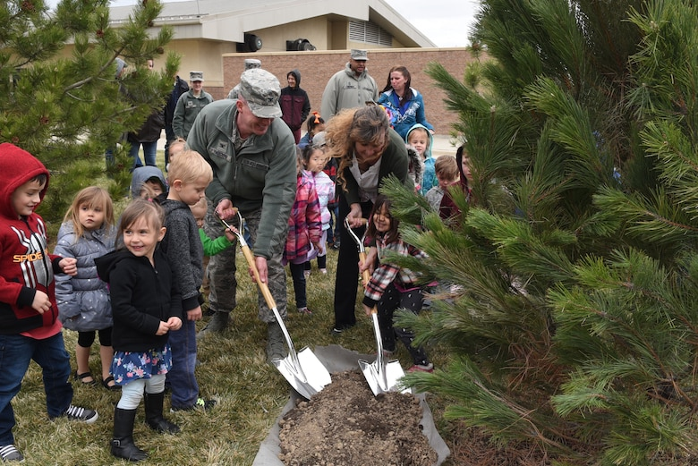 Col. Troy L. Endicott, 460th Space Wing commander, and Ms. Nancy Klasky, a member of the Community Forestry Division for Colorado State, ceremoniously pour dirt on a pine tree planted in honor of Arbor Day, April 26, 2018, on Buckley Air Force Base, Colorado. Children from the Child Development Center participated in the event by helping pour dirt around the base of the tree as well. (U.S. Air Force Photo by Senior Airman Jessica B. Kind)