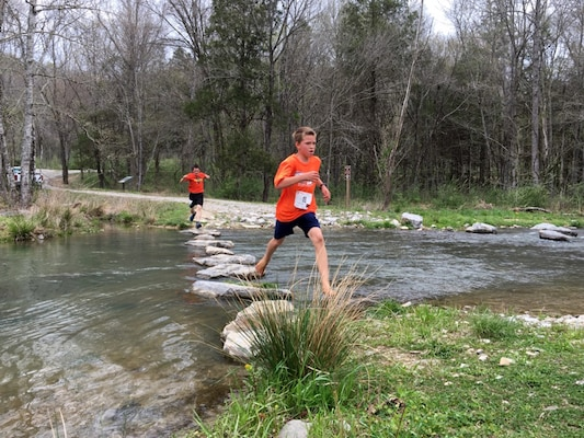 A few young boys run across Hatchery Creek in Jamestown, Ky., during the third annual Trout Trot 5K April 14, 2018 at the Wolf Creek National Fish Hatchery and Kendal Recreation Area below Wolf Creek Dam. The event also kicked off the recreation season at Lake Cumberland, which is operated by the U.S. Army Corps of Engineers Nashville District. (USACE photo by Park Ranger Cody Pyles)