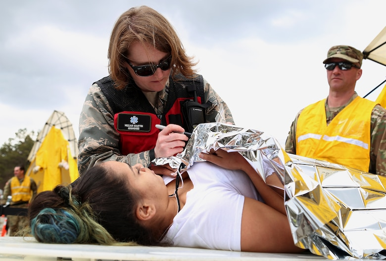 Capt. Megan C. Martin, a nurse assigned to the 157th Medical Group, N.H. Air National Guard, documents the condition of a simulated casualty onto a triage card during a deployment readiness exercise on April 11, 2018 at Joint Base Cape Cod, Mass. Martin is a member of the New England CBRNE Enhanced Response Force Package team. (N.H. Air National Guard photo by Staff Sgt. Kayla White)