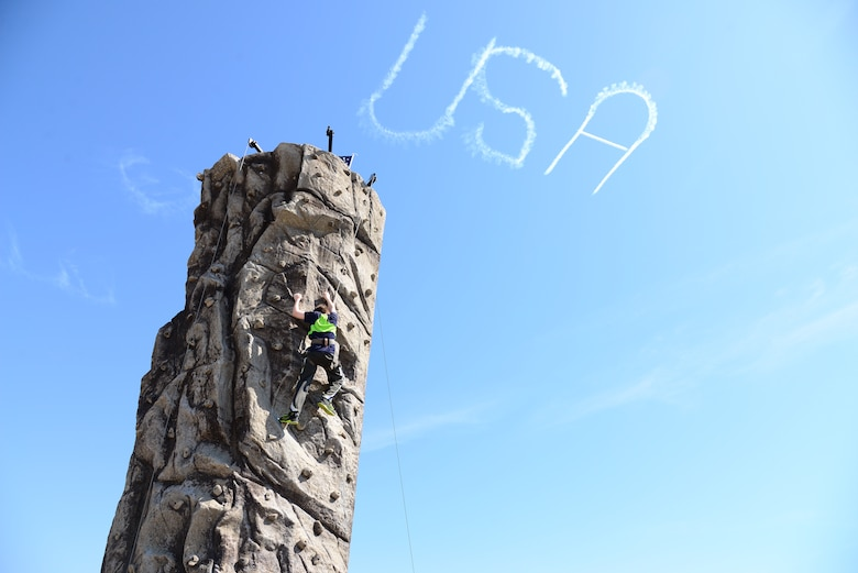 "A young man climbs a rock wall while a plane draws ""USA"" in the sky during 2018 Wings Over Columbus April 21, 2018 at Columbus Air Force Base, Mississippi. Along with the aerial performances, rock-climbing and other carnival-type attractions were present at the air show. (U.S. Air Force photo by Airman 1st Class Beaux Hebert)"