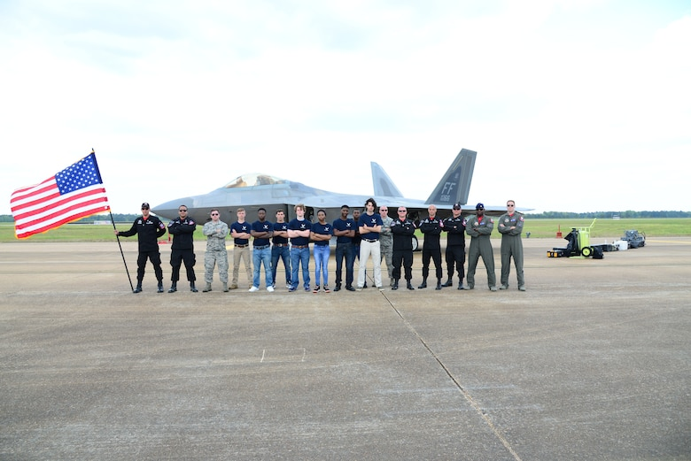 Eight Delayed Entry Program recruits, two Air Force recruiters and the Air Combat Command F-22 Raptor Demonstration team stand in front of an F-22 during 2018 Wings Over Columbus Air and Space Show April 21, 2018, at Columbus Air Force Base, Mississippi. The recruits took the oath of enlistment, administered by Maj. Paul Lopez, ACC F-22 Demonstration team pilot, during the air show. (U.S. Air Force photo by Airman 1st Class Beaux Hebert)