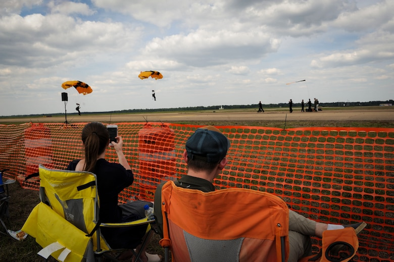Spectators watch as members of the U.S. Army Golden Knights make their way to the ground on Columbus Air Force Base, Mississippi, April 21, 2018, during the Wings Over Columbus Air and Space Show. The Golden Knights are the Army's premier parachute team. (U.S. Air Force photo by Tech. Sgt. Christopher Gross)