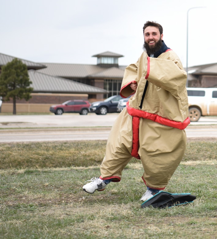 Jacob Garrett, an education liaison at the Airmen and Family Readiness Center, runs a lap in a sumo suit at Ellsworth Air Force Base, S.D., April 20, 2018. One of the key events of Sexual Assault Awareness and Prevention Month was the Sexual Assault Prevention and Response race that six team's participated in. (U.S. Air Force photo by Airman 1st Class Thomas Karol)
