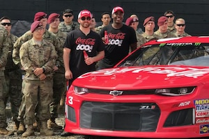 Two civilians stand for a photo with soldiers in front of a red NASCAR car.