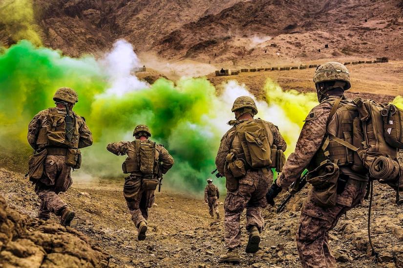Marines run down a hill toward green smoke.