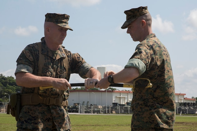 Sgt. Maj. Jim Lanham, out-going sergeant major of the 31st Marine Expeditionary Unit, relinquishes the sword of office to Col. Tye R. Wallace, commanding officer of the 31st MEU, during his relief and appointment ceremony at Camp Hansen, Okinawa, Japan, April 27, 2018.