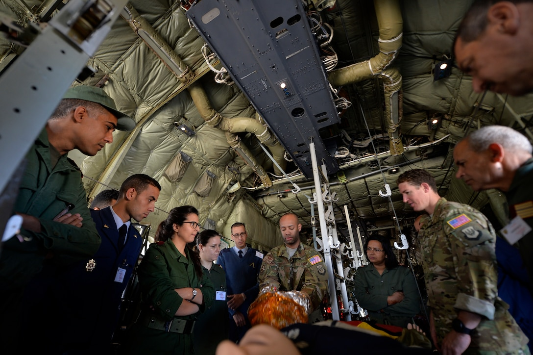 U.S. Air Force Senior Airman Kyle Pacheco, 86th Aeromedical Evacuation Squadron AE technician, center, demonstrates use of an emergency passenger oxygen system during Exercise African Lion 2018, April 19, 2018, at Kenitra Air Base, Morocco. Service members from the Moroccan Royal Armed Forces observed and practiced AE procedures to further develop one another's capabilities, allowing both nations to operate more efficiently in the event of a contingency operation. (U.S. Air Force photo by Staff Sgt. Nesha Humes Stanton)