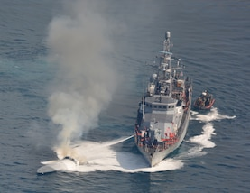 USS Zephyr conducts ship-to-ship firefighting to extinguish a fire aboard a low-profile go-fast vessel.