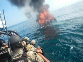 suspected smuggler who jumped from his burning vessel, in background, is pulled aboard an interceptor boat.