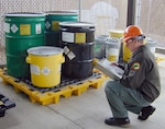 A DLA contractor prepares for the removal of hazardous waste to be removed from a DoD generator site.
