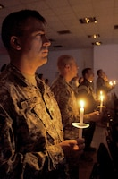 Army Capt. Jeffrey Daley and other service members celebrate Christmas Eve during a candlelight service in Gilbert Memorial Chapel at Joint Base Balad, Iraq. Daley is the officer in charge of administrative support for the 51st Expeditionary Signal Battalion, which is deployed from Fort Lewis, Washington.
