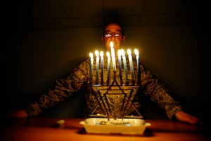 Air Force Capt. Andrew Cohen, chaplain, stands behind a lit menorah during the eighth night of Hanukkah at Joint Base Balad, Iraq. Jewish military chaplains receive a full range of religious supplies from DLA