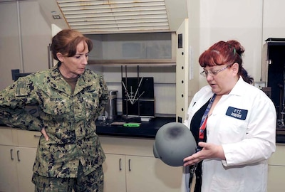 DLA Land and Maritime Commander Navy Rear Adm. Michelle Skubic discusses the results of blunt-force-impact testing for helmets with DLA lab technician Sally Schuster during a visit to Mechanicsburg, Pennsylvania.