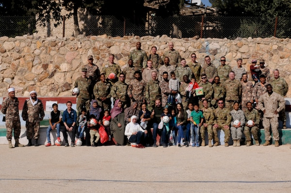 Members of the U.S. military and Jordan Armed Forces pose with workers, relatives and of residents of the Amman SOS Children's Village April 23. They were all part was part of a donation visit to the village that was arranged by Jordan Armed Forces Imams in coordination with U.S. Chaplains as part of ongoing coordination between the two partner nation militaries. Events like these help to build trust between service members and citizens of different nations.