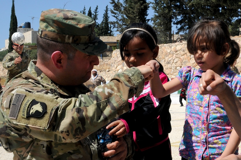 U.S. Army Maj. John Salazar, an information operations officer with U.S. Army Central teaches a resident of the Amman SOS Children's Village how to do a fist bump April 23. Salazar was part of a donation visit to the village that was arranged by Jordan Armed Forces Imams in coordination with U.S. Chaplains as part of ongoing coordination between the two partner nation militaries. Events like these help to build trust between service members and citizens of different nations.
