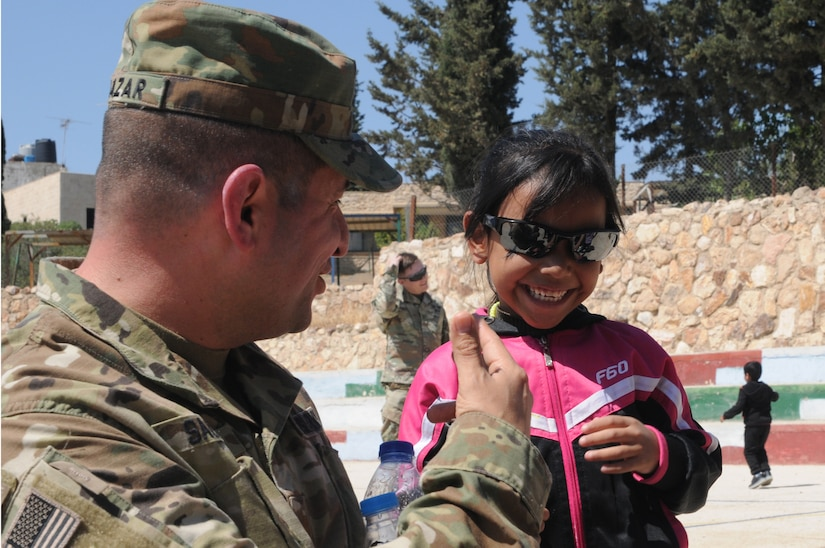 U.S. Army Maj. John Salazar, an information operations officer with U.S. Army Central lets a resident of the Amman SOS Children's Village try on his sunglasses  April 23. Salazar was part of a donation visit to the village that was arranged by Jordan Armed Forces Imams in coordination with U.S. Chaplains as part of ongoing coordination between the two partner nation militaries. Events like these help to build trust between service members and citizens of different nations.