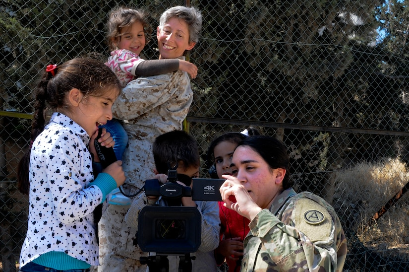 U.S. Army Spc. Nicholle Salvatierra, a public affairs broadcast specialist with U.S. Army Central, shows residents of the Amman SOS Children's Village how her video camera works as U.S. Navy Chaplain (Lt. Cmdr.) Victoria Chappell, Naval Amphibious Forces, Task Force 51 and 5th Marine Expeditionary Forces Brigade looks on April 23. They were part of a donation visit to the village that was arranged by Jordan Armed Forces Imams in coordination with U.S. Chaplains as part of ongoing coordination between the two partner nation militaries. Events like these help to build trust between service members and citizens of different nations.