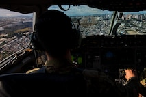 Lt. Col. Corey Akiyama, 21st Airlift Squadron C-17 Globemaster III pilot, flies Denton Program emergency response vehicles to La Aurora International Airport, Guatemala City, Guatemala, April 20, 2018. The Denton Program is a Department of Defense transportation program that moves humanitarian cargo, donated by U.S. based non-governmental organizations to developing nations to ease human suffering. The emergency vehicles were donated by the Mission of Love Foundation. They are the largest user of the Denton Program, having delivered medical, relief and humanitarian supplies to needy communities throughout the world. (U.S. Air Force photo by Master Sgt. Joey Swafford)