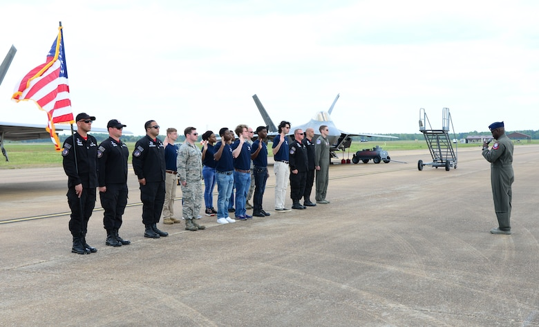 Eight recruits take the oath of enlistment, administered by Maj. Paul Lopez, Air Combat Command's F-22 Demonstration Team pilot, during the 2018 Wings Over Columbus Air and Space Show April 21, 2018, on Columbus Air Force, Base, Mississippi. The recruits were positioned in front of the F-22 Raptor display, one of which took part in an aerial demonstration during the air show. (U.S. Air Force photo by Airman 1st Class Beaux Hebert)