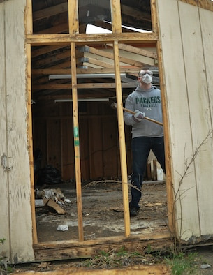 Airman Basic Kyler, fusion analyst with the 29th Intelligence Squadron, contemplates his next move during the destruction of a dilapidated storage shed as part of a renovation project with the Maryland Wing of the Civil Air Patrol headquarters that was severely damaged in winter storms. Over 20 airmen from the Squadron have volunteered more than 200 hours collectively towards this restoration project.  (U.S. Air Force photo by Tech. Sgt. Mark Thompson)