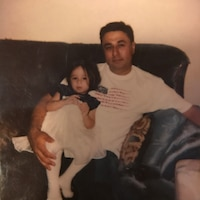 Melissa Cerna, then three years old, and now-retired Air Force Master Sgt. Jose Cerna, her father, sit on a couch in Abilene, Texas.