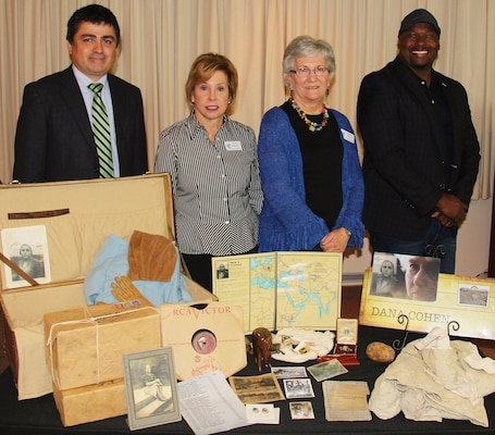 IMAGE: VIRGINIA BEACH, Va. (April 25, 2018) - Vivian Margulies and Lynn Woods of the United Jewish Federation of Tidewater pause at a table filled with mementoes and reproductions from the life of Dana Cohen during a commemoration held at Naval Surface Warfare Center Dahlgren Division Dam Neck Activity. Margulies and Woods spoke about the life of Cohen - a Hampton Roads resident - in their presentation entitled, 'What We Carry', to military and civilian personnel commemorating Holocaust Remembrance Day. NSWCDD Dam Neck Activity engineer Roberto Garcia and Equal Employment Opportunity specialist Marcus Matthews coordinated the visit. Standing left to right are Garcia, Margulies, Woods and Matthews. For more on Cohen's story, visit http://jewishva.org/node/746.