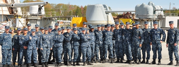 IMAGE: DAHLGREN, Va. (April 26, 2017) - U.S. Naval Academy Midshipmen and their instructors are pictured during their tour of the gun line at the Potomac River Test Range where naval guns have been tested since 1918. Throughout their Naval Surface Warfare Center Dahlgren Division (NSWCDD) visit, the future officers were briefed on technologies related to their course of study at the U.S. Naval Academy Weapons and Systems Engineering Department. Navy civilian scientists and engineers briefed the Midshipmen on electromagnetic launchers, hypervelocity projectiles, and directed energy weapons, in addition to the command's capabilities in complex warfare systems development and integration to incorporate electric weapons technology into existing and future fighting forces and platforms. This marks the Naval Academy's 17th tour of NSWCDD since 2009. Over the past 10 years, 572 Midshipmen toured Dahlgren - including the 30 Midshipmen who toured the command today - for briefings relative to their courses of study. In all, three Naval Academy instructors accompanied the Midshipmen, on this tour. Behind the Midshipmen are, left to right, a retired eight-inch triple mount automatic gun mount; a 76mm/62caliber super rapid gun mount; a retired eight-inch/55 major caliber automatic gun mount; a retired five-inch Mark 42/10 mount; and the five-inch/54 caliber automatic gun mount with the test gun barrel removed for inspection. (U.S. Navy photo/Released)