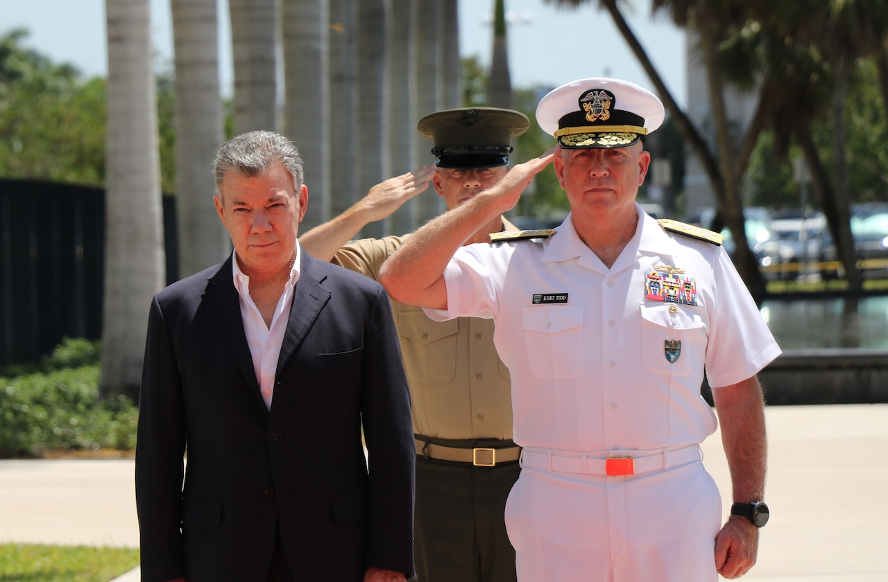Navy Adm. Kurt W. Tidd, right, commander of U.S. Southern Command, and Marine Corps Sgt. Maj. Bryan Zickefoose, Southcom's command sergeant major, salute during the playing of the U.S. and Colombian national anthems as Colombian President Juan Manuel Santos, left, listens during a welcoming ceremony at Southcom's headquarters in Miami.