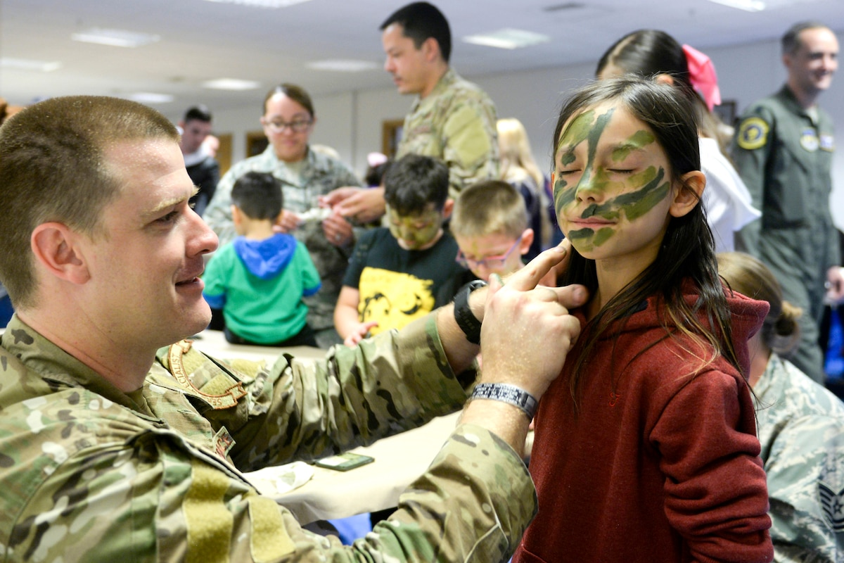 An airman puts green face paint on a child.