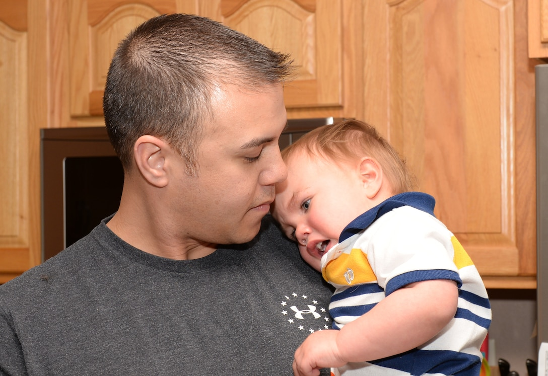 Tech. Sgt. Brian Thomas, the 28th Civil Engineer Squadron noncommissioned officer in charge of power production, comforts his son at home in Box Elder, S.D., April 19, 2018. The family has been involved with supporting community youth programs and working in orphanages for more than 10 years. (U.S. Air Force photo by Airman 1st Class Nicolas Z. Erwin)