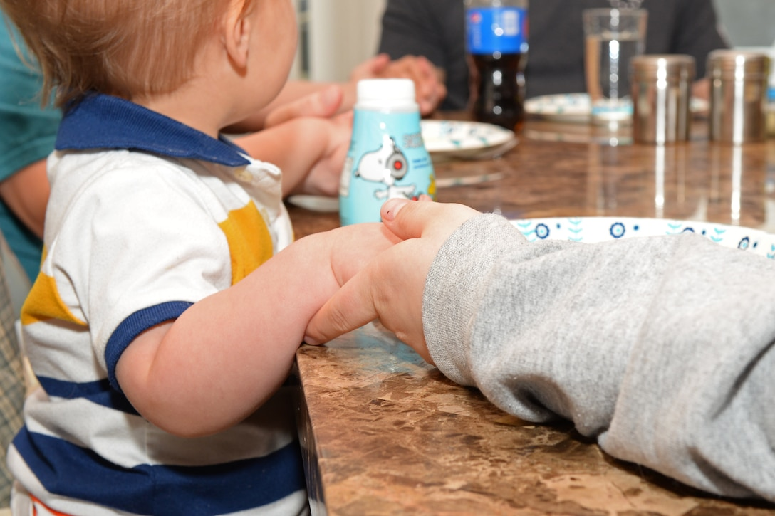 Tech. Sgt. Brian, the 28th Civil Engineer Squadron noncommissioned officer in charge of power production, and Tech. Sgt. Leah Thomas, noncommissioned officer in charge of Quality Assurance, Aircrew Flight Equipment, hold hands with their son Lucas as they say grace at their home in Box Elder, S.D. The family has had some of their previous foster children visit and participate in family functions whenever they are in the area. (U.S. Air Force photo by Airman 1st Class Nicolas Z. Erwin)