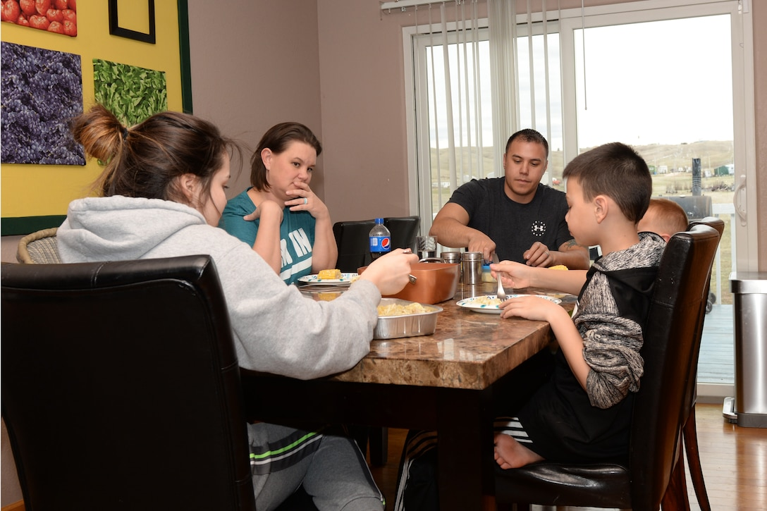 Tech. Sgt. Brian, the 28th Civil Engineer Squadron noncommissioned officer in charge of power production,  and Tech. Sgt. Leah Thomas, a 28th Operations Support Squadron noncommissioned officer in charge of Quality Assurance, Aircrew Flight Equipment, eat dinner with their children at their home in Box Elder, S.D., April 19, 2018. Brian and Leah have been involved with mentoring youth for over 10 years in the United States and in other countries. (U.S. Air Force photo by Airman 1st Class Nicolas Z. Erwin)