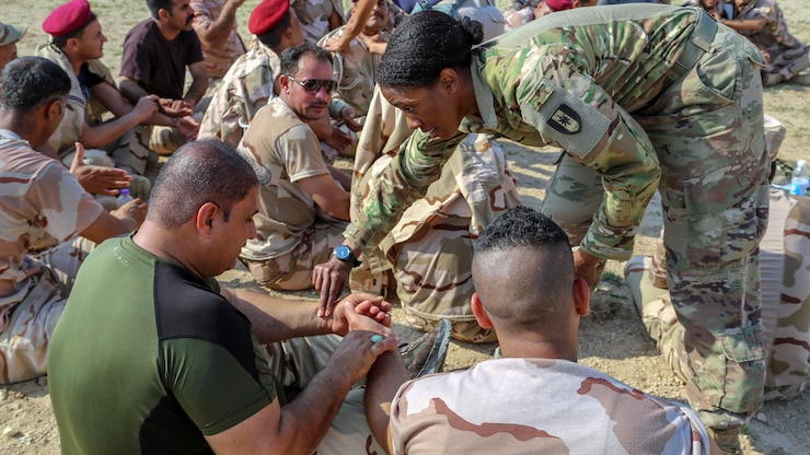 A soldier places her hand on another person's wrist.