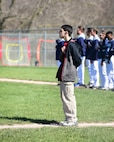 Andy Martins, a manager for the Warrensburg High School baseball team, stands with his hand over his heart during the playing of the national anthem before a game at West Park in Warrensburg, Mo., April 16, 2018. Growing up with autism, Andy has used sports as a way to strength his communication and socialization skills. (U.S. Air Force photo by Staff Sgt. Danielle Quilla)