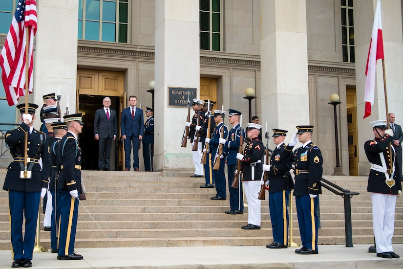 Defense Secretary James N. Mattis stands with Polish Defense Minister Mariusz Blaszczak on steps leading to a Pentagon entrance, flanked by troops.