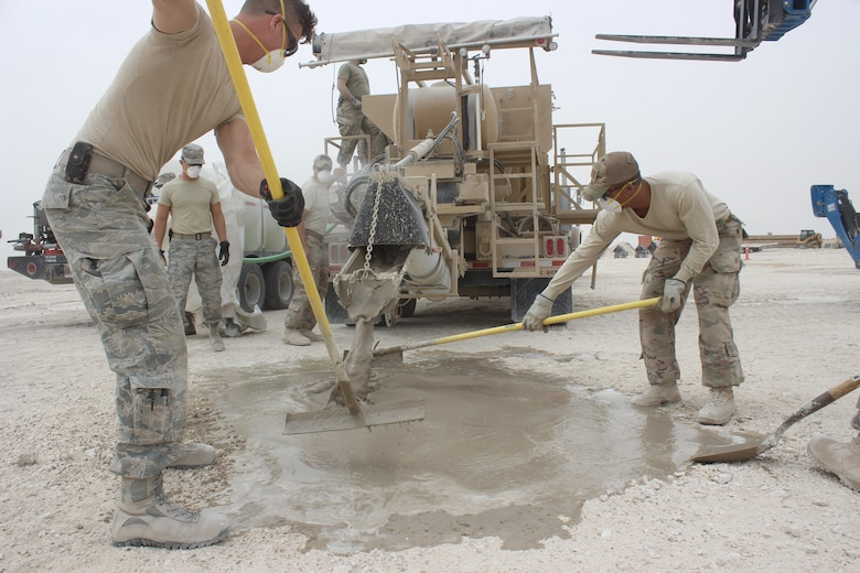 Civil engineers level concrete that caps a crater on a mock airfield at Al Udeid Air Base, Qatar on April 25, 2018. The machinery, a simplified volumetric mixer, expedites the time of mixing and placing concrete into craters on damaged airfields. Rapid Airfield Damage Recovery (RADR) is a new six-step concrete and asphalt repair process enhancing the ability of civil engineers to more rapidly repair airfields. Civil engineers can now guarantee repairs to full operational capability in a matter of hours. This is also the first time RADR has been utilized in AFCENT.(U.S. Air Force photo by Tech. Sgt. Arthur Mondale Wright)