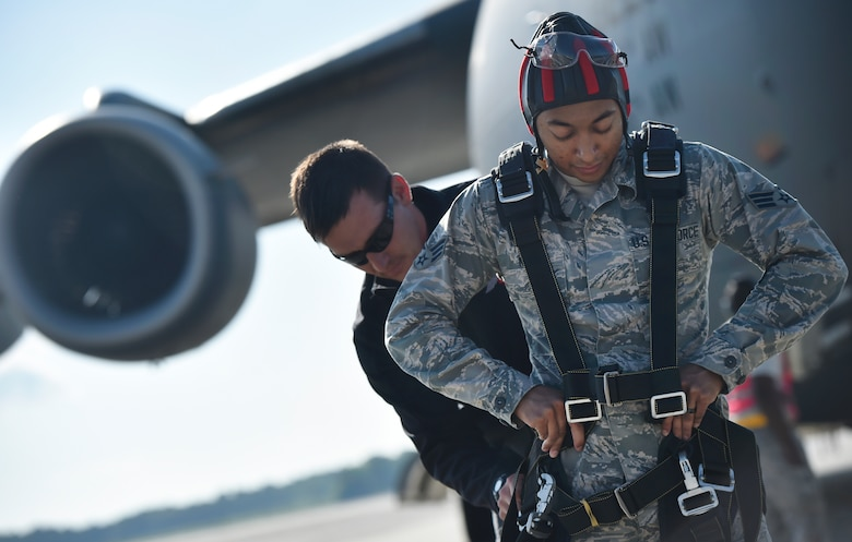 """U.S. Army Sgt. 1st Class Sean O'Toole, U.S. Army Special Operations Command Parachute Demonstration Team, known as the """"Black Daggers,"""" fastens harness equipment to U.S. Air Force Senior Airman Keyren King, 628th Communications Squadron, prior to performing a practice tandem jump as part of a 2018 Air and Space Expo rehearsal April 27, 2018, at Joint Base Charleston, S.C."""