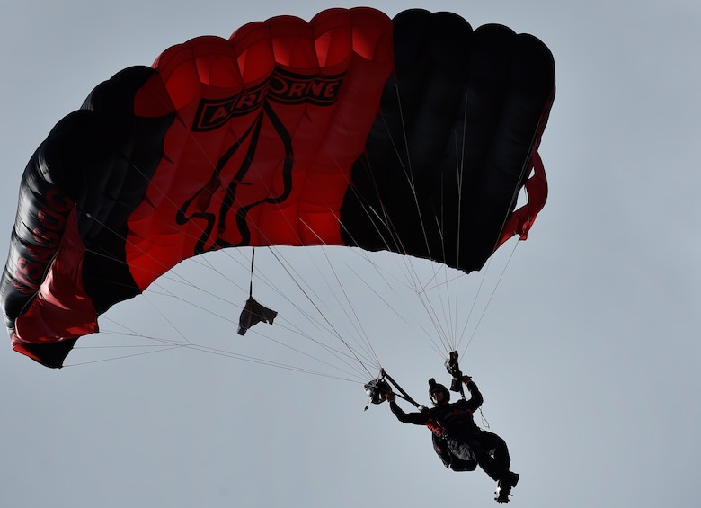 """A Soldier from the U.S. Army Special Operations Command Parachute Demonstration Team, known as the """"Black Daggers,"""" parachutes down to a drop zone as part of a 2018 Air and Space Expo rehearsal April 27, 2018, at Joint Base Charleston, S.C."""
