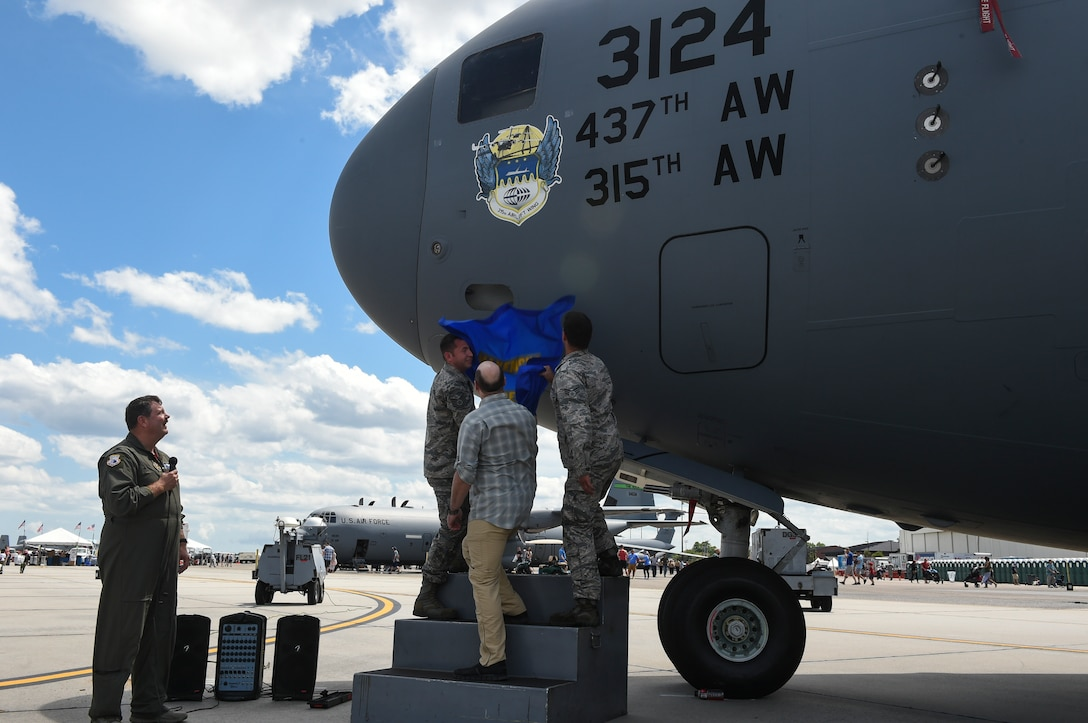 Members of the 315th Airlift Wing reveal the nose art on a C-17 Globemaster III during rehearsal of the Air and Space Expo, April 27, 2018.