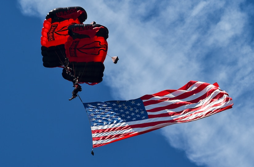 A U.S. Army Special Operations Command Black Daggers Parachute Demonstration Team member flies the American Flag during the National Anthem before the Air & Space Expo at Joint Base Charleston, S.C., April 28, 2018.