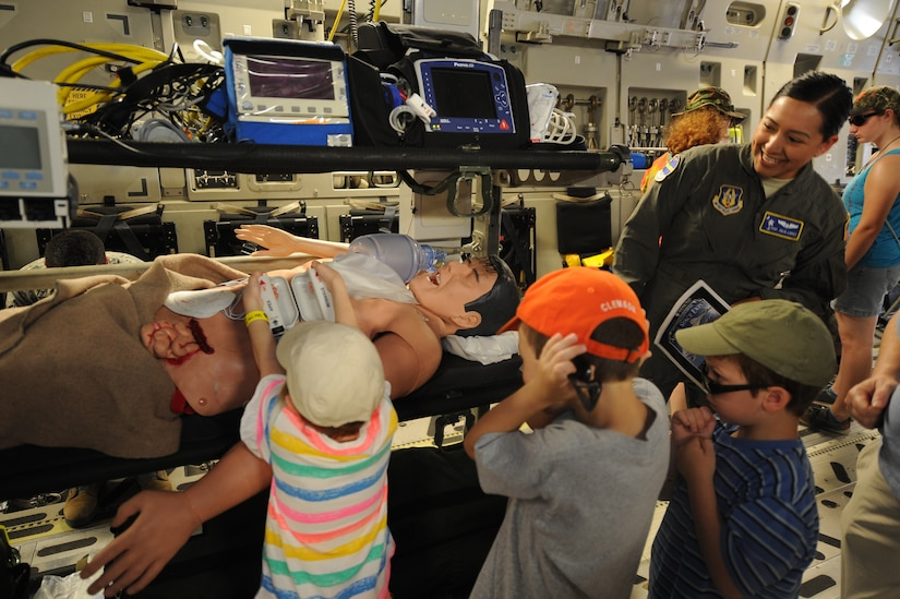 Tech. Sgt. Julia Lopez from the 315th Aeromedical Evacuation Squadron, shows children how defibrillator paddles work while on a C-17 Globemaster III during the Air and Space Expo April 28, 2018, at Joint Base Charleston, S.C.
