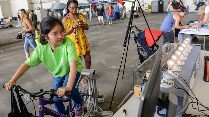 A young girl peddles a bike to power lights during an electrical demonstration at the Joint Base Charleston Air and Space Expo,  JB Charleston, S.C.  Apr 28, 2018.