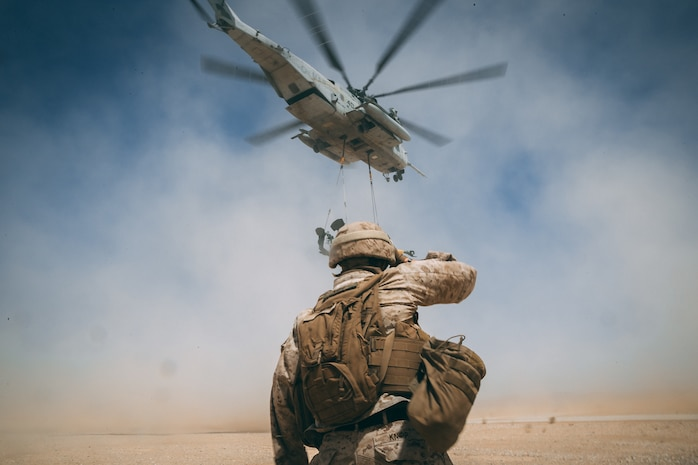 A Marine with combat logistics battalion 8, 2 marine logistics group watches a CH-53E Super Stallion carry away M777 Howitzer at Sand hill Marine Corps Air Ground Combat Center, Twentynine Palms, Calif., Apr 27, 2018, as a part of Integrated Training Exercise 3-18. The purpose of ITX is to create a challenging, realistic training environment that produces combat-ready forces capable of operating as an integrated MAGTF.