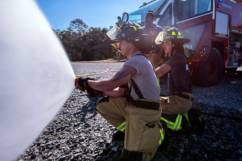 Firefighters from the 23d Civil Engineer Squadron (CES) spray a hose during live-fire training, April 24, 2018, at Moody Air Force Base, Ga. Firefighters from the 23d CES and Valdosta Fire Department participated in the training to gain more experience fighting aircraft fires and to work together as a cohesive team while still practicing proper and safe firefighting techniques. (U.S. Air Force photo by Airman Eugene Oliver)