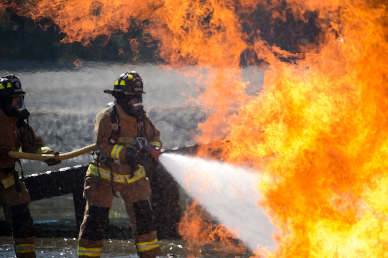 Firefighters from the Valdosta Fire Department (VFD) extinguish an aircraft fire during live-fire training, April 24, 2018, at Moody Air Force Base, Ga. Firefighters from the 23d Civil Engineer Squadron and VFD participated in the training to gain more experience fighting aircraft fires and to work together as a cohesive team while still practicing proper and safe firefighting techniques. (U.S. Air Force photo by Airman Eugene Oliver)