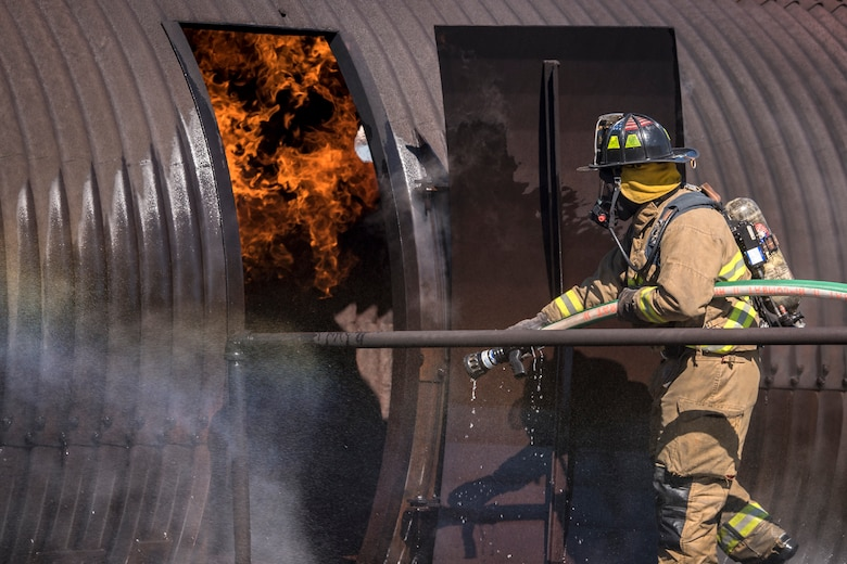 A firefighter from the Valdosta Fire Department (VFD) enters a simulated aircraft during live-fire training, April 25, 2018, at Moody Air Force Base, Ga. Firefighters from the 23d Civil Engineer Squadron and VFD participated in the training to gain more experience fighting aircraft fires and to work together as a cohesive team while still practicing proper and safe firefighting techniques. (U.S. Air Force photo by Airman Eugene Oliver)
